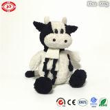 Vache à Noël se reposant doucement avec le jouet de peluche d'écharpe