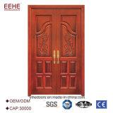 Puertas exteriores de madera dobles principales de la entrada con las tallas