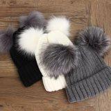 方法アクリルのポンポンが付いているクリスマスによって編まれる帽子の帽子