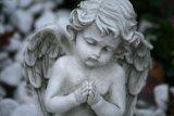 Scultura di pietra di angelo che intaglia modellando il marmo grigio di pietra del granito del leone