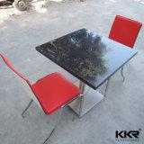 人工的な石造りの正方形のレストランのテーブルの上のダイニングテーブル