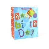 O brinquedo azul da roupa do aniversário calç os sacos de papel do presente das lembranças dos ofícios