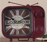 型の装飾的で旧式な赤TVの形の金属のテーブルの上のクロック