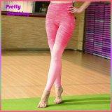 La ragazza variopinta ha stampato i pantaloni di yoga di goccia di usura di yoga di sport