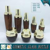 輝いた金のふたが付いているこはく色の化粧品ガラスクリーム色の瓶およびガラスビン