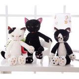 La peluche scherza i giocattoli bianchi ed il gatto nero