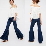 Le pantalon élevé de jeans comporte une patte épanouie avec un bord cru