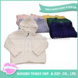 아기 카디건이 회백질 검정에 의하여 뜨개질을 한 스웨터에 의하여 농담을 한다