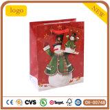 El verde rojo del muñeco de nieve de la Navidad arropa la bolsa de papel del regalo