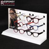 魅力的なデザインガラスの棚のアクリルおよびポスターが付いているPVCカウンタートップのサングラスの陳列台