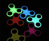 Fingerspitzen in der dunklen Drehung der rastlose LED-Handspinner