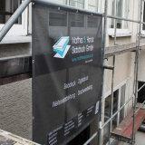 Aufbau-Gebäude wickelt Zaun-Ineinander greifen-Fahne für das Bekanntmachen des Zeichens ein