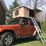 陸上で道のトレーラーの手段車の堅い屋根の上のテントを離れてキャンプする4WD SUV