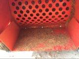Le coperture della noce di cocco che scheggiano la palma della macchina lasciano lo sfibratore di legno