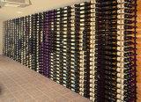 Cremalheira fixada na parede do vinho do indicador do frasco com a cremalheira dos vidros de vinho