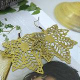 O cobre antigo da cor do ouro cinzelado torna ôco para fora o brinco da folha de plátano