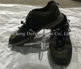 La mano usada talla grande barata de los zapatos segundos calza los zapatos del deporte