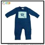 濃紺の男の子のロンパースに着せている暖かい冬の赤ん坊