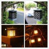 L'attaccatura solare esterna della lanterna illumina in su la candela tremula della lampada impermeabile del giardino