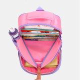 O estudante da escola preliminar caçoa o saco de escola encantador cor-de-rosa das meninas
