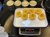Amarelo em conserva as metades de pêssegos em calda