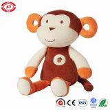 ブラウン猿の着席動物はギフトのプラシ天の柔らかいおもちゃをからかう