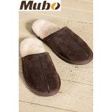 暖かい冬の屋内羊皮のスリッパの人の靴