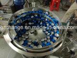 Botellas del frasco que llenan tapando la máquina que capsula