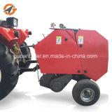 機械トラクターによって取付けられる小型ラウンド・ベーラを束ねる農場の干し草