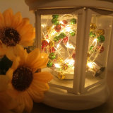 Свет пробочки бутылки вина, свет шнура рождества с цветастыми колоколами