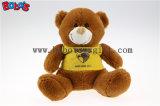 """7 """" 노란 t-셔츠를 가진 장난감 장난감 곰이 암갈색 주문품 아기에 의하여 농담을 한다"""