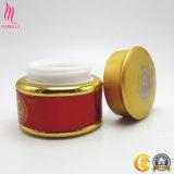 クリーム色のパッキングのための美しい金帽子が付いている金および赤いカラー瓶