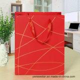 Bolso de papel rojo del regalo con la cuerda de rosca del oro