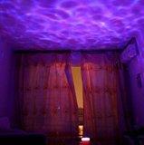 Proiettore di luce di notte dell'oceano con le onde blu del mare del giocatore di musica