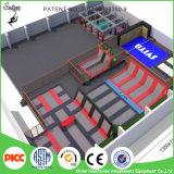 Capretti che rimbalzano la grande sosta rotonda del trampolino della Camera con gli adulti dell'interno dell'arena del campo da giuoco di allegato