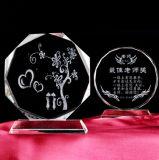 緑の葉が付いている円形のクリスタルグラスのトロフィ賞