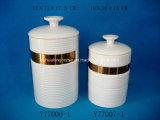 Un insieme di 3 contenitori chiusi ermeticamente di ceramica variopinti con il coperchio di legno
