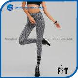 Le gris folâtre le pantalon en bonne santé de yoga d'élastique de guêtres de femmes haut