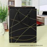 Bolso de papel negro del regalo con la cuerda de rosca del oro
