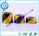 La seguridad amarilla y negra de la precaución del tráfico sujeta con cinta adhesiva la cinta de la barrera