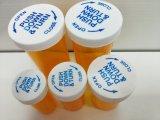 Los frascos reversibles del envase de la píldora de la medicina empujan hacia abajo y dan vuelta a los frascos