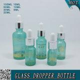 O frasco de vidro cosmético azul transparente de petróleo essencial com transferência introduz com pipeta o conta-gotas de olho