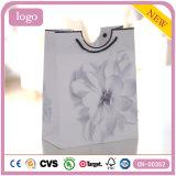 A flor branca calç o saco de papel do presente dos artigos de papelaria do brinquedo da roupa