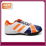 人のスポーツの運動屋内はサッカーの靴をひもで締める