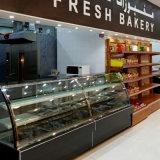 A loja da padaria curvou a porta de vidro de deslizamento no refrigerador dianteiro do indicador da sobremesa/bolo