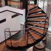 Escalera de acero con las pisadas de madera y el pasamano del acero inoxidable