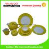 Il padellame di ceramica giallo ha impostato con il piattino della tazza ed il POT del latte
