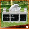 Angelo del bambino nella base nera di marmo bianca del granito di Carrara