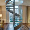 Trilhos de vidro curvados internos da casa de campo que cerc a escadaria espiral com o passo de escadas do metal