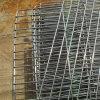 La griglia del BBQ gratta la rete metallica